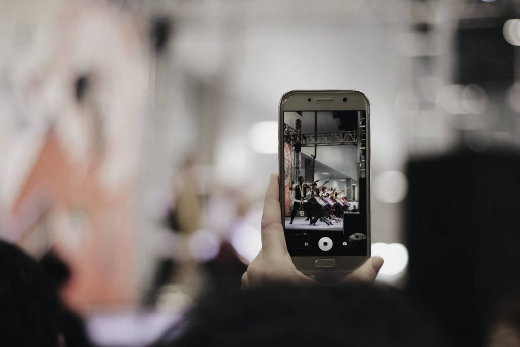 Man holding a phone taking a picture to engage with others on Instagram.