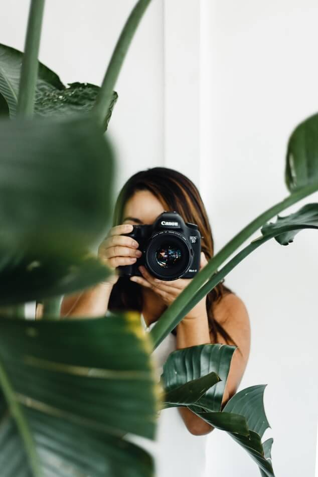 Instagram influencer taking a picture with a DSLR camera behind a plant.
